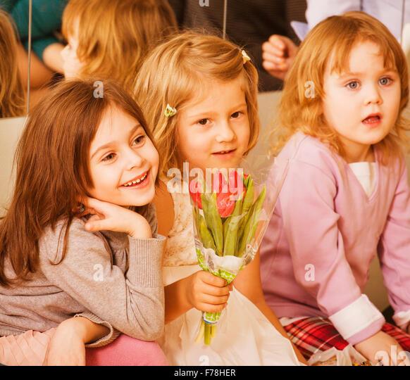 three little diverse girls at birthday party having fun - Stock-Bilder