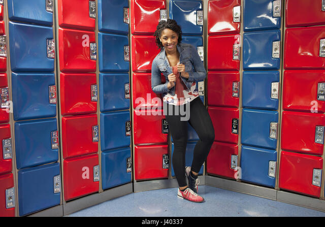 A young woman by some red and blue lockers. - Stock Image