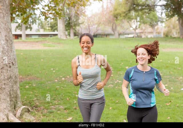 Full length front view of women wearing sport clothing running on grass smiling - Stock Image