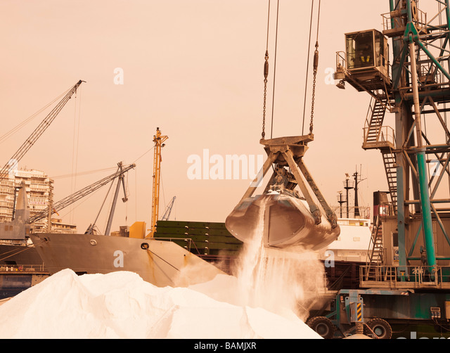 Harbour crane lifting phosphates into ship in Malaga port, Spain; Crane lifting phosphates into ship - Stock-Bilder