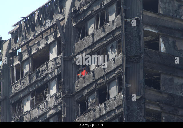 London, UK. 16th June, 2017 - Firefighters in red hIgh Visibility coats seen inspecting the charred remains of the - Stock Image