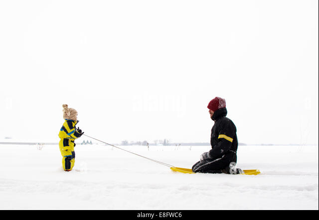 Son pulling father on sledge (2-3 years) - Stock Image
