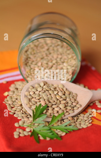 Lentils in a glass with a wooden spoon - Stock Image