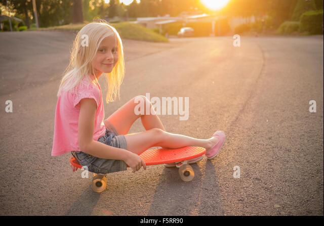 Sweden, Smaland, Anderstorp, Portrait of girl (8-9) sitting on red shortboard in street - Stock Image