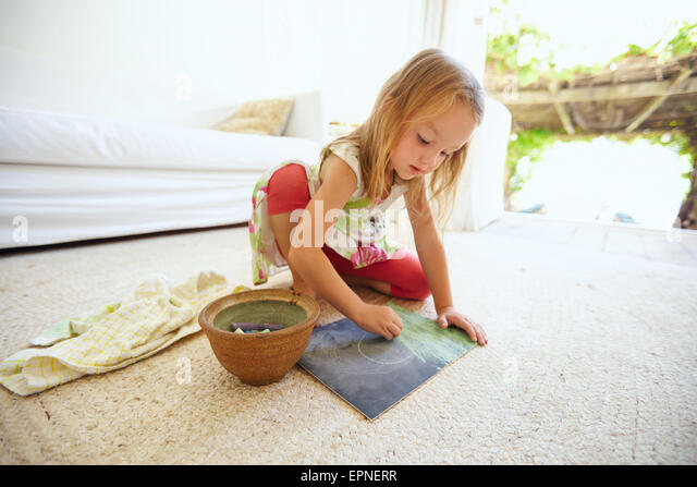 Shot of innocent little caucasian girl sitting on floor coloring a picture with color chalks. Schoolgirl drawing - Stock Image