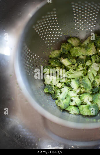 chopped broccoli in strainer. sink, kitchen, vegetable, food. - Stock Image