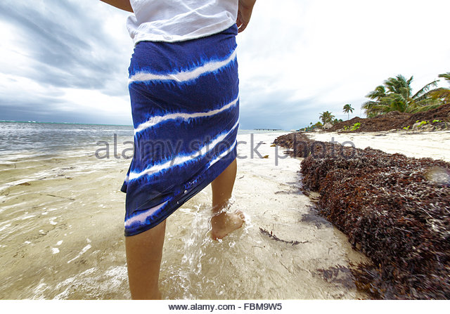 Girl walking in the surf, Belize - Stock Image