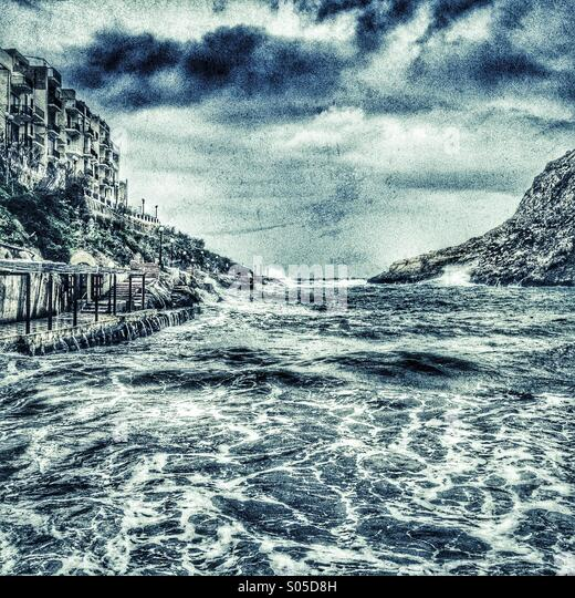 Storm seas lashing into small harbour - Stock Image