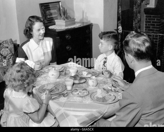 1940s 1950s FAMILY MOTHER FATHER BOY GIRL EATING SUPPER AT DINING TABLE - Stock Image