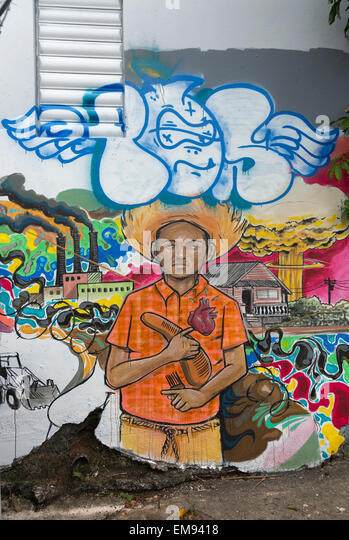 Political graffiti of young man surrounded by environmental disasters. - Stock Image