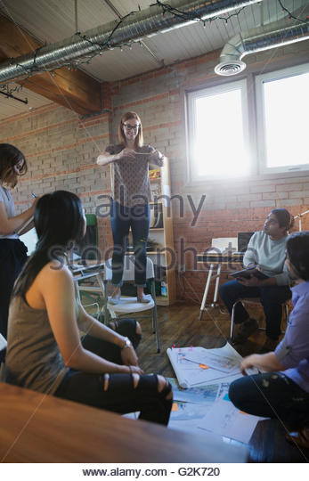 Designer standing on chair photographing proofs on office floor - Stock Image