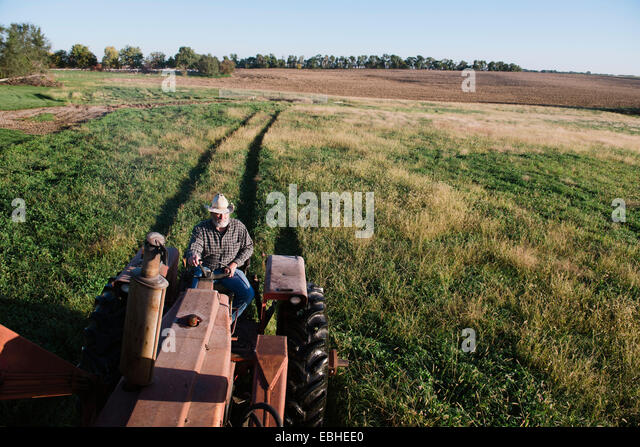 High angle view of senior male farmer driving tractor in field, Plattsburg, Missouri, USA - Stock Image