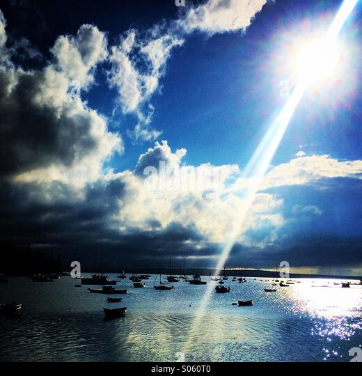 Sunset over a harbor in brooklin, Maine with boats in the harbor - Stock Image