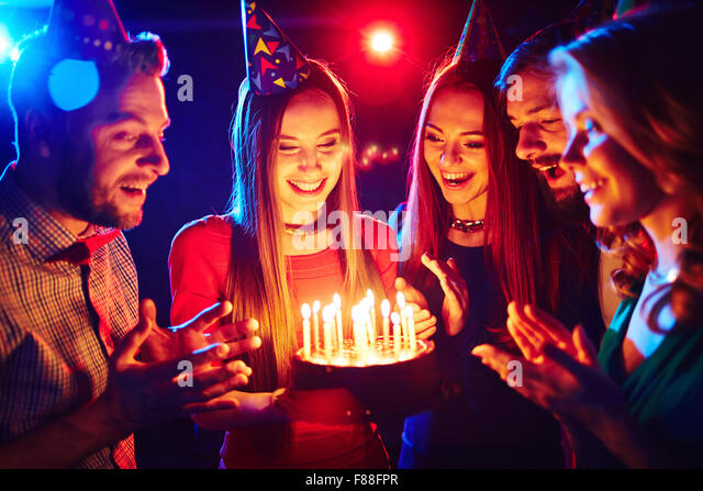 Happy young friends celebrating birthday - Stock Image