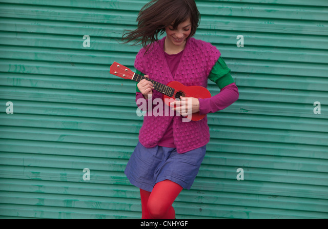 Young woman playing ukulele - Stock Image