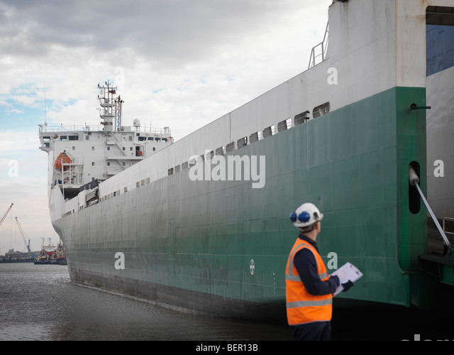 Port Worker Looking At Container Ship - Stock-Bilder