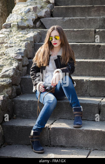 Young fashion woman with photo camera sitting on the stairs. Attractive caucasian girl in city outdoors - Stock Image