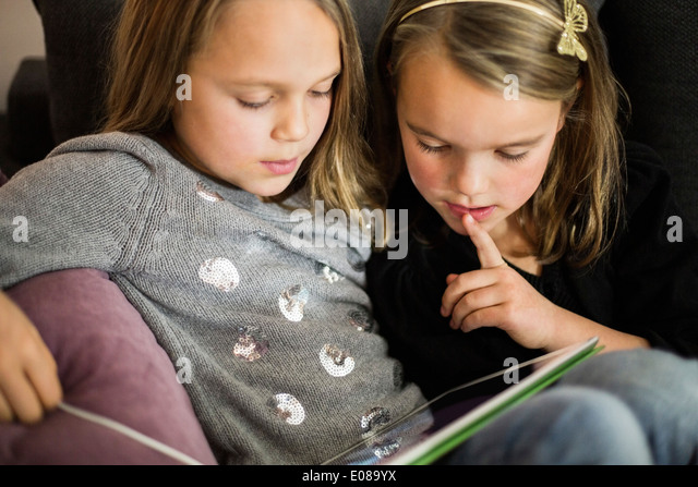 Sisters using digital tablet together at home - Stock Image