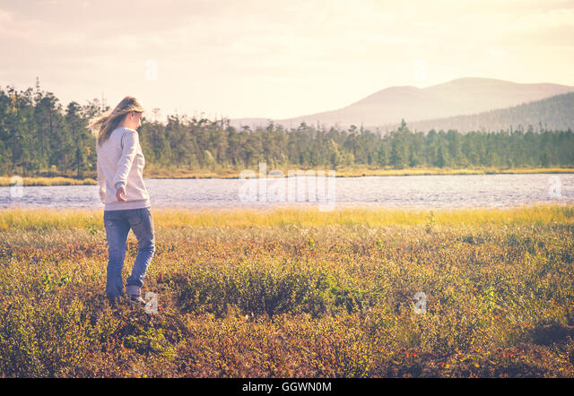 Woman Traveler walking alone Travel Lifestyle concept Summer vacations outdoor tundra forest on background - Stock Image