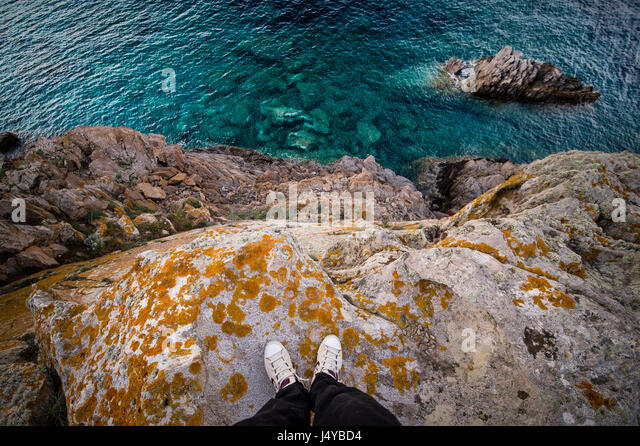 A man standing on a high cliff of an Italian coast with the Mediterranean sea Below him. Porto Cervo - Emerald Coast, - Stock Image