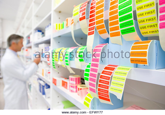Labels in foreground and pharmacist looking for medication on pharmacy shelf - Stock Image
