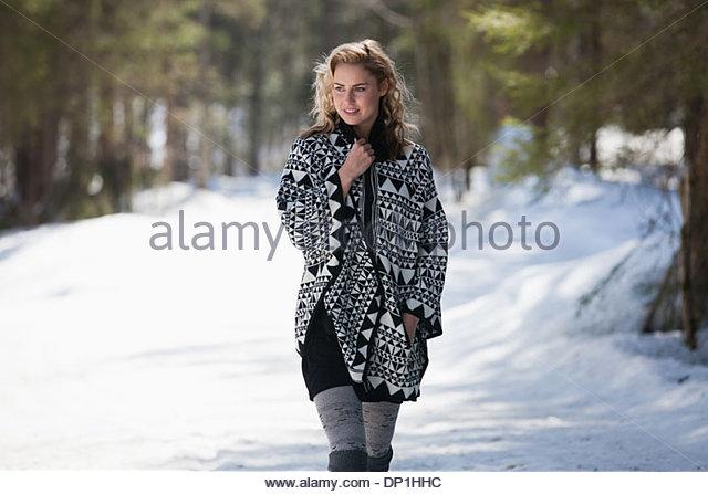 Woman walking in snow - Stock Image