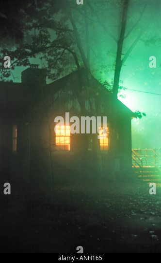 Lone cabin in the woods at Big Meadows Lodge Shenandoah National Park Virginia with inside lights on and eerie green - Stock-Bilder