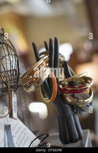 A display of rings and bangles, and objects in an antique store. - Stock Image
