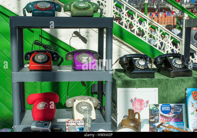 Old fashioned rotary telephones for sale on a market stall. - Stock Image