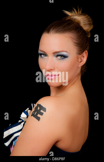 Beautiful young woman with a chinese tattoo wearing blue makeup and pink lipstick - Stock-Bilder