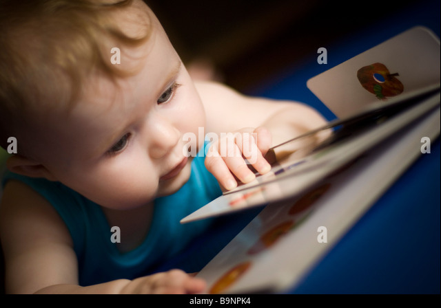 Baby reading book - Stock Image