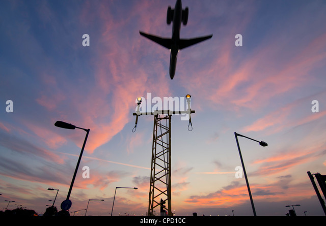 DC9 aircraft approaching over runway landing light gantries at sunset, London, England, United Kingdom, Europe - Stock Image