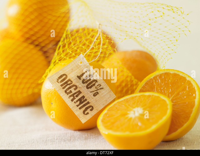 A bag of organic oranges on a beige fabric surface. - Stock Image
