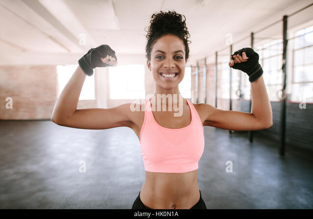 Portrait of young fitness woman flexing muscles and smiling. African female model in sportswear showing her muscles. - Stock Image