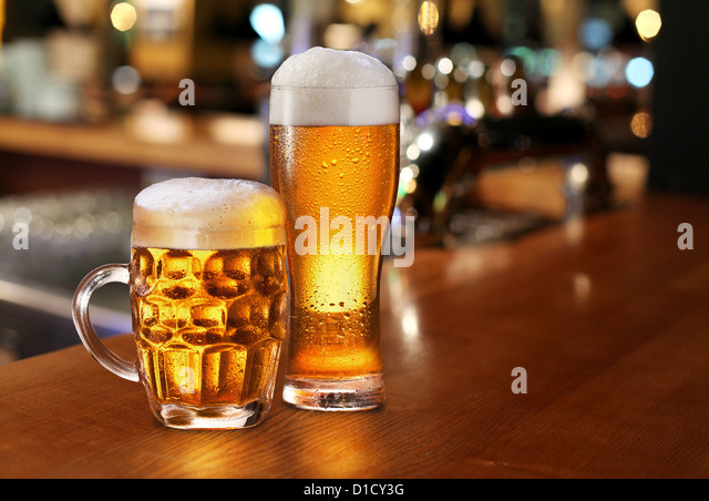 Glass of light beer on a dark pub. - Stock Image