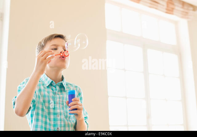 Boy blowing bubbles at home - Stock Image