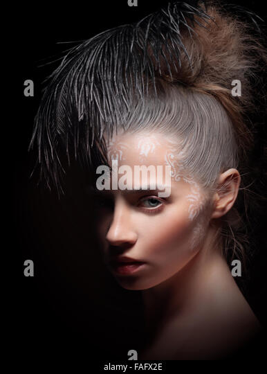 Beautiful woman with  feather. Art make-up. - Stock Image