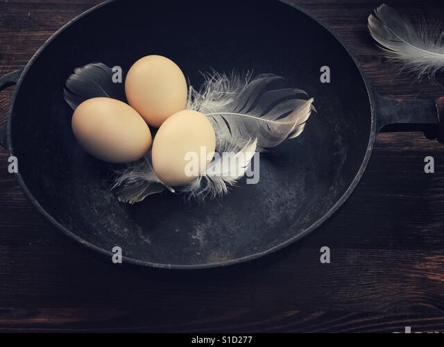 Three chicken eggs in a black cast-iron frying pan - Stock-Bilder