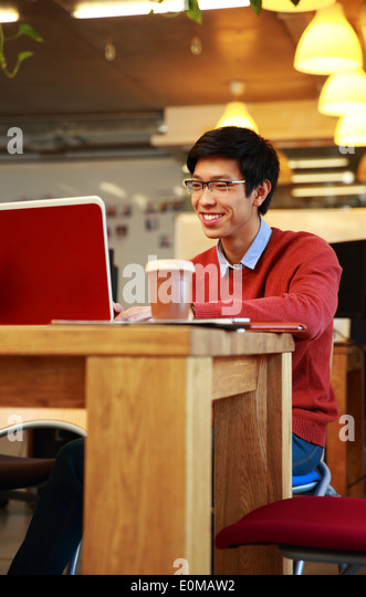 Smiling asian man in glasses working on laptop - Stock Image
