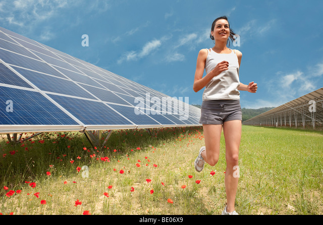 woman jogging along solar panel - Stock Image
