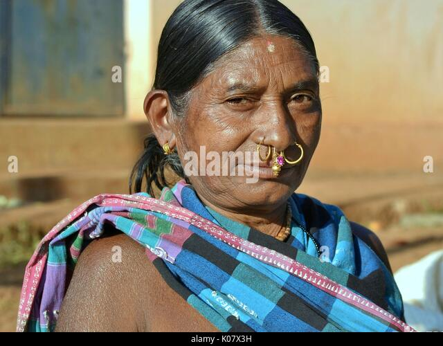 Elderly Indian Adivasi market woman with two golden nose rings, one piece of precious gold-and-gemstone nose jewellery - Stock Image