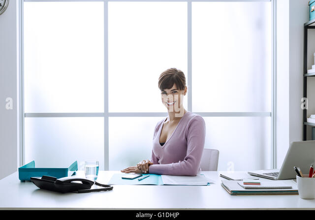 Confident smiling young businesswoman in her office, she is looking at camera and sitting at desk - Stock-Bilder