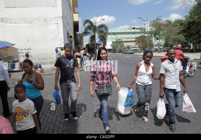 Santo Domingo Dominican Republic Calle Ravelo street corner intersection Hispanic Black man woman boy teen shopping - Stock Image