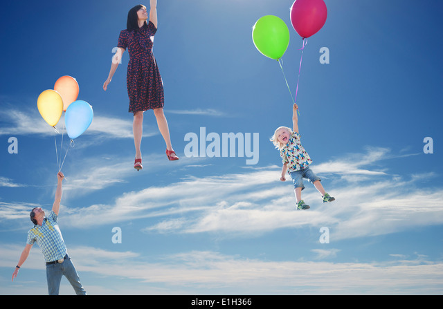 Mature couple and young son floating skyward holding onto balloons - Stock Image