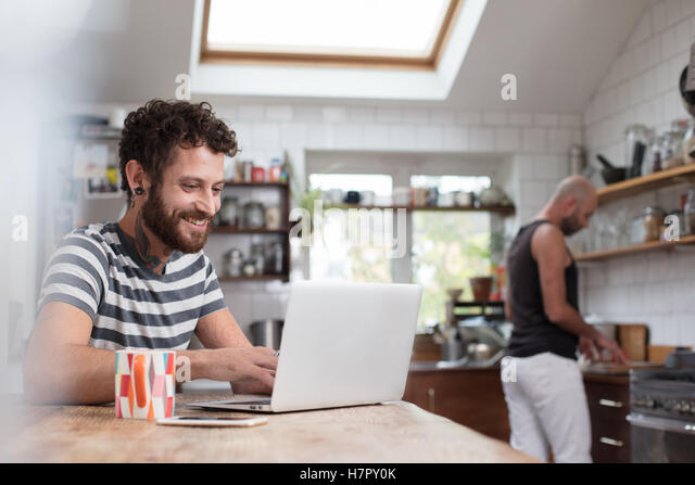 Gay couple using laptop and cooking in kitchen - Stock-Bilder