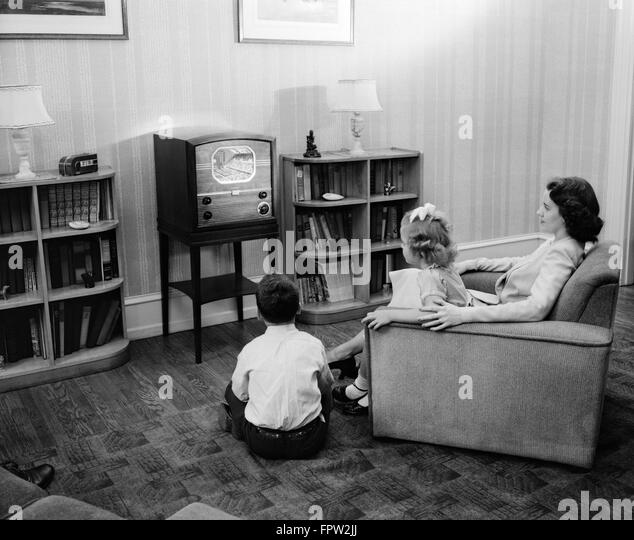 1940s 1950s MOTHER BOY GIRL WATCHING TELEVISION IN FAMILY LIVING ROOM - Stock Image