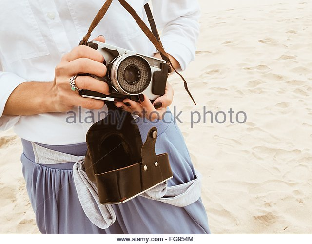 Midsection Of Woman Holding Old-Fashioned Camera At Beach - Stock-Bilder