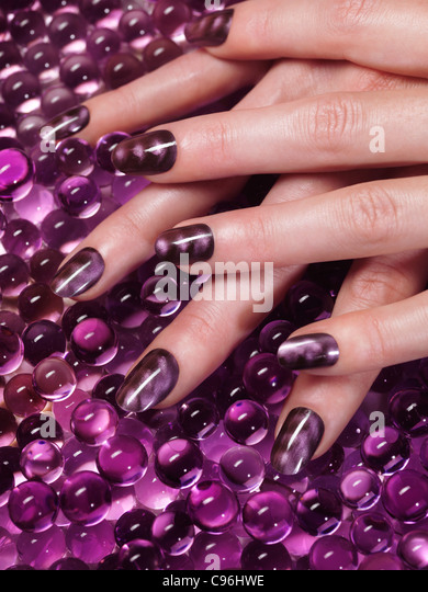 Closeup of woman hand with custom design purple nail polish on abstract purple background - Stock Image