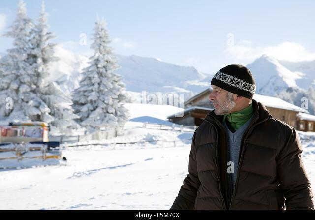 Waist up of senior man and snow covered trees looking away, Sattelbergalm, Tyrol, Austria - Stock Image