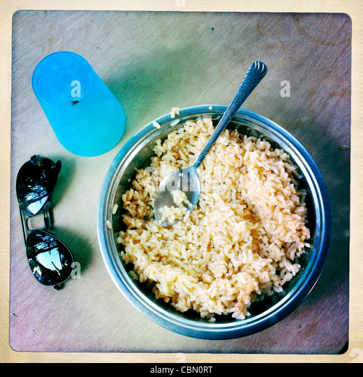 Silvery Bowl Of Rice Sunglasses And Plastic Glass On A Table Lughaya Somaliland - Stock Image